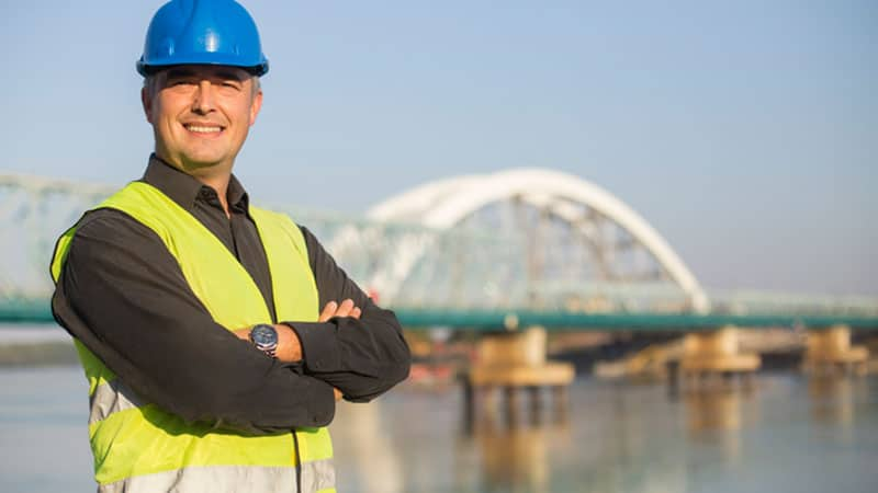 Construction Worker Smiling In Front Of Bridge In The Background.