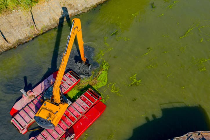 Top down view of dredging on water.